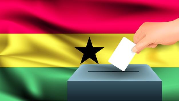 La mano maschio mette giù un foglio di carta bianco con un segno come simbolo di una scheda elettorale sullo sfondo della bandiera del ghana. il ghana il simbolo delle elezioni