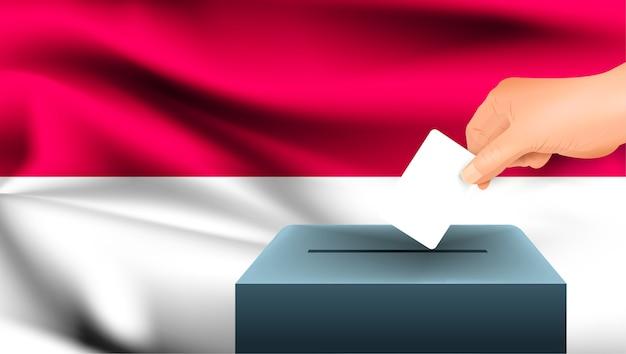 La mano maschio mette giù un foglio di carta bianco con un segno come simbolo di una scheda elettorale sullo sfondo della bandiera dell'indonesia. indonesia il simbolo delle elezioni
