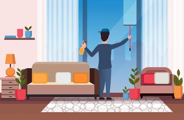 Bidello maschio con doccia tergicristallo e spray bottiglia di plastica detergente uomo pulizia vetro pulizia finestra concetto moderno soggiorno interno a figura intera piano orizzontale