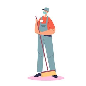 Bidello maschio che indossa maschera medica mentre spazza il pavimento