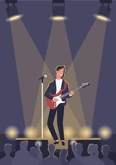Un musicista maschio che suona la chitarra elettrica nelle luci del palcoscenico.