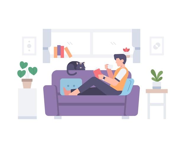 Un maschio leggendo un libro e bevendo una tazza di caffè caldo sul divano con il suo gatto in una casa