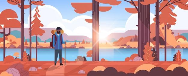 Viandante turistica maschio con il bastone della tenuta del viaggiatore dell'uomo dello zaino che sta nella foresta che fa un'escursione integrale orizzontale del fondo delle montagne del fiume della natura di paesaggio di autunno di concetto