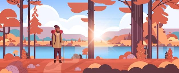 Viandante turistica maschio con il bastone della tenuta del viaggiatore dell'uomo dello zaino che sta nella foresta che fa un'escursione le montagne del fiume della natura del paesaggio di autunno di alba di concetto