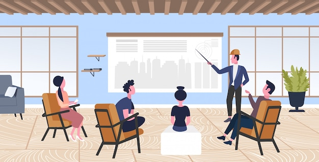 Uomo architetto facendo ingegnere di presentazione che presenta il nuovo modello di città di costruzione ai colleghi durante la riunione conferenza panning urbano concetto di progetto moderno disegnatore studio interno a figura intera orizzontale