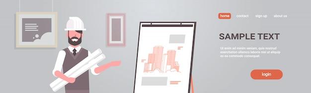 Architetto uomo nel casco in possesso di progetti in rotoli ingegnere che mostra la nuova costruzione di disegno su cavalletto