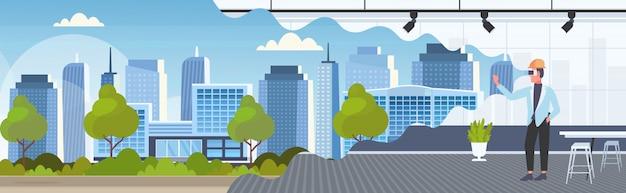 Architetto uomo nel casco con gli occhiali digitali realtà virtuale 3d edificio città modello vr modellazione cuffia concetto visione moderno ufficio interno orizzontale integrale