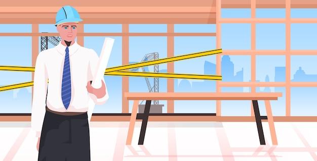 Uomo builder con progetto blueprint ingegnere nel casco lavorando al concetto di servizio di riparazione del sito di costruzione incompiuto edificio interno ritratto orizzontale