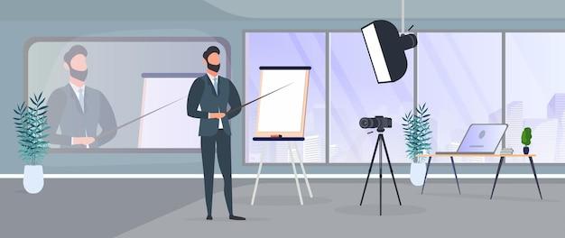 Un uomo in giacca e cravatta con una cravatta sta facendo una presentazione alla telecamera. l'insegnante sta scrivendo una lezione. il concetto di blogging, formazione online e conferenze. fotocamera su treppiede, softbox.