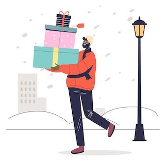 L'uomo porta una pila di regali di natale per salutare con le vacanze invernali e la celebrazione del nuovo anno