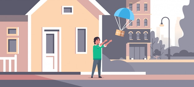 Uomo che cattura la scatola pacchi cadendo con il paracadute dal cielo trasporto pacchetto di spedizione posta aerea espresso concetto di consegna moderna casa edificio esterno a figura intera orizzontale piatta