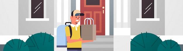 Uomo corriere nel tappo che trasportano fast food ordine ragazzo con zaino e pacchetto di prodotti in carta consegna espressa dal negozio o ristorante concetto moderno edificio esterno piatto orizzontale ritratto