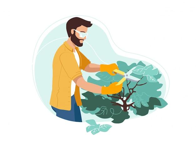 Equipaggi i cespugli di taglio sul suo cortile in guanti e occhiali protettivi. hobby o professione di giardinaggio all'aperto.
