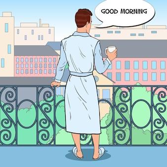 Uomo che beve caffè sul balcone