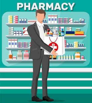 Uomo che tiene la borsa della farmacia davanti al negozio della farmacia. Vettore Premium