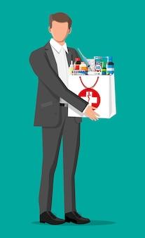 Uomo che tiene la borsa della farmacia. set di flaconi, compresse, pillole, capsule e spray per la malattia