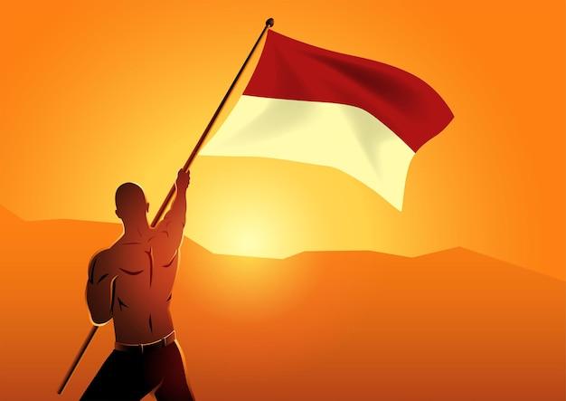 Uomo che tiene la bandiera dell'indonesia giorno dell'indipendenza 17 agosto 1945