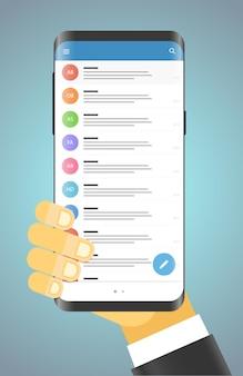 Uomo che tiene in mano uno smartphone moderno app di messaggistica moderna per smartphone