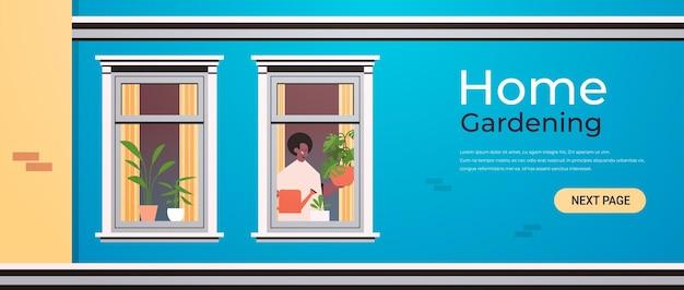 Uomo che tiene annaffiatoio e versa piante concetto di giardinaggio domestico ragazzo afroamericano che si prende cura di piante d'appartamento in casa finestra ritratto orizzontale copia spazio illustrazione