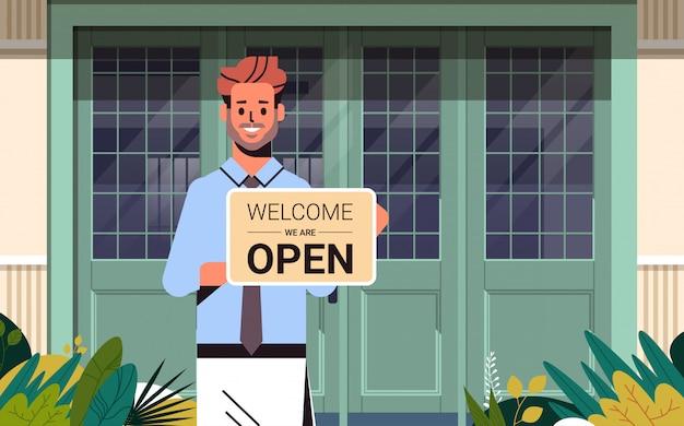 Man holding welcome siamo segno aperto