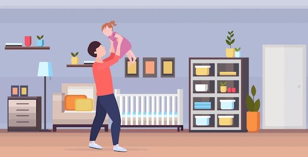 Uomo che alza il suo piccolo bambino lei e sua figlia che giocano divertendosi felice concetto di paternità familiare moderno bambino camera da letto interno integrale orizzontale