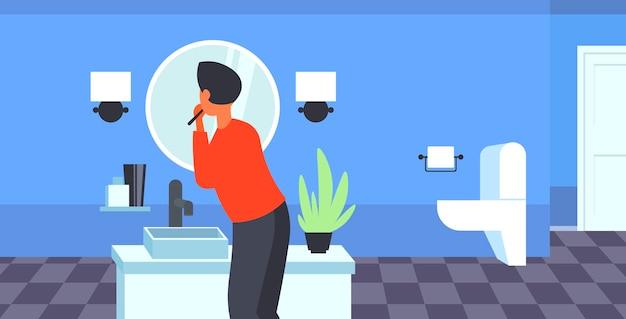 Uomo che guarda allo specchio lavarsi i denti con spazzolino da denti sanità igiene dentale concetto moderno bagno interno vista posteriore ritratto