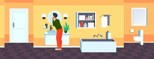 Uomo che guarda allo specchio lavarsi i denti con spazzolino da denti sanità igiene dentale concetto moderno bagno interno vista posteriore
