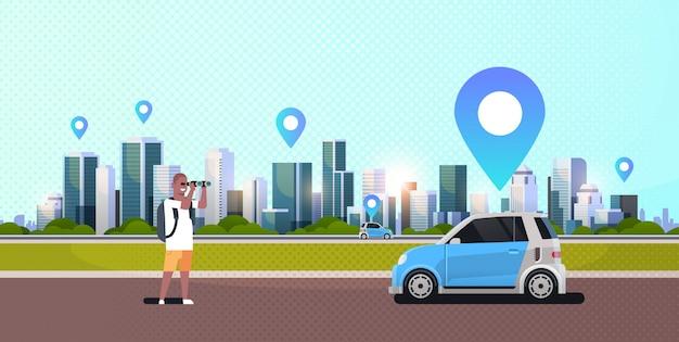 Uomo che osserva tramite il binocolo alla ricerca orizzontale di sfondo moderno di paesaggio urbano di servizio di car sharing di concetto di car sharing di trasporto del veicolo dell'automobile