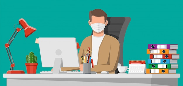 Uomo in maschera medica lavorando sul suo computer