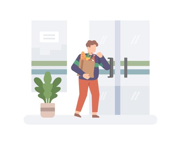 Un uomo che apre una porta usando l'illusione del gomito dopo lo shopping al supermercato o alla drogheria