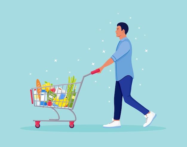 Uomo che spinge il carrello pieno di generi alimentari al supermercato. c'è un pane, bottiglie d'acqua, latte, frutta, verdura e altri prodotti nel cestino