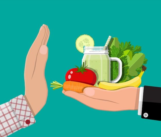L'uomo rifiuta di prendere cibo sano con un gesto della mano. rifiutare cibi crudi o vegetariani.