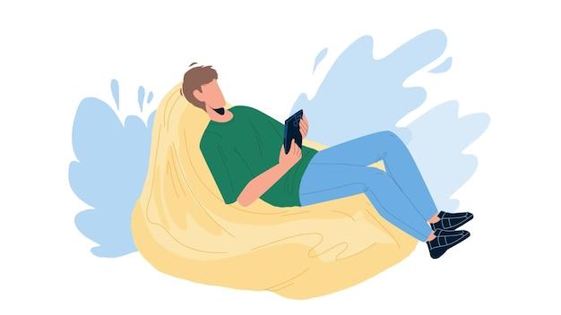L'uomo si rilassa sul sacco di fagioli e gioca sul vettore del telefono. il giovane ragazzo ha tempo libero e si rilassa sul divano morbido. personaggio libero professionista uomo d'affari che si rilassa dopo il lavoro piatto fumetto illustrazione