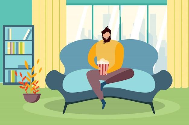 L'uomo siede la finestra del divano con il secchio del popcorn guarda la tv