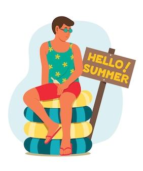 L'uomo si siede sul mucchio dell'anello gonfiabile con il cartello di legno con le parole ciao estate