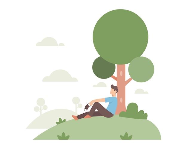 Un uomo seduto da solo sotto un grande albero mentre tiene una maschera per il viso per sfuggire alla pandemia di coronavio dopo un mese di isolamento