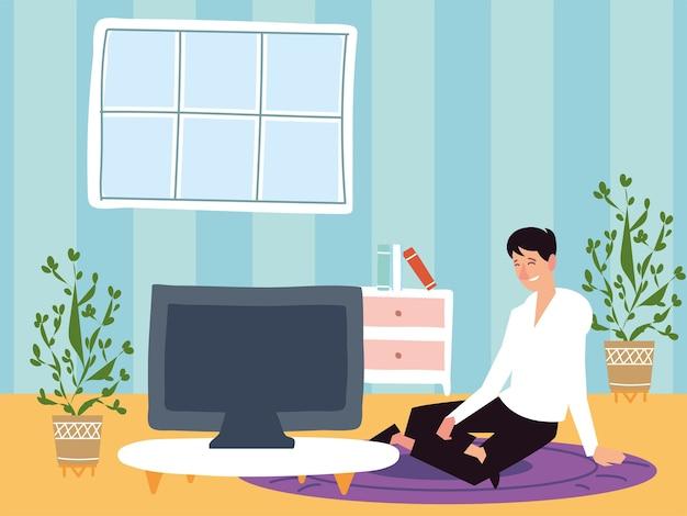 Uomo seduto su un tappeto utilizzando il computer lavora da casa, attività indoor