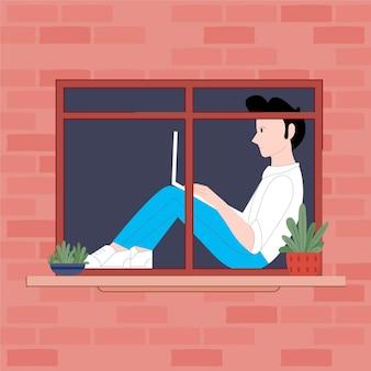 Uomo seduto con un computer portatile sul davanzale della finestra