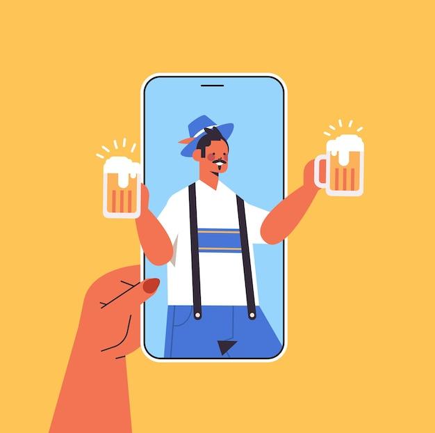 Uomo sullo schermo dello smartphone che tiene il boccale di birra oktoberfest party