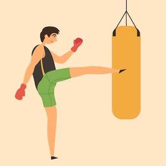 L'uomo colpisce il sacco da boxe con i piedi