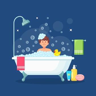 Uomo che fa il bagno in bagno con anatra di gomma. lavare i capelli, il corpo. vasca da bagno piena di schiuma con bolle