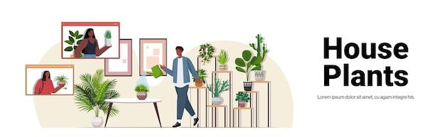 Uomo che si prende cura di piante d'appartamento che hanno incontro virtuale con ragazze afroamericane durante la videochiamata soggiorno interno copia spazio orizzontale