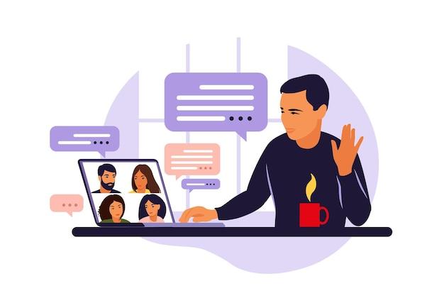 Uomo che utilizza il computer per riunioni virtuali collettive e videoconferenze di gruppo. uomo al desktop in chat con gli amici in linea. videoconferenza, lavoro a distanza, concetto di tecnologia.