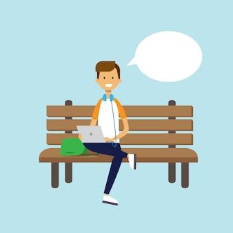 Uomo che per mezzo del computer portatile che si siede il carattere di bolla di chiacchierata del banco di legno integrale su fondo blu piano