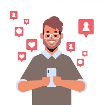 Uomo che per mezzo dell'applicazione mobile su notifiche di smartphone con like, follower, commenti, ritratto di concetto di dipendenza digitale della rete di social media