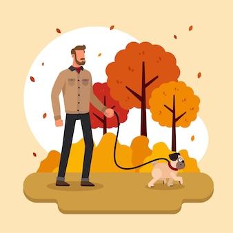 Uomo che cammina il suo cane in autunno