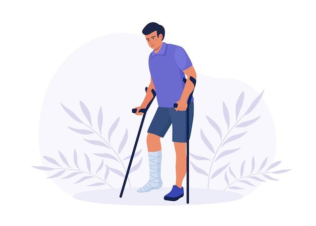 Uomo che cammina con gamba rotta in gesso con stampelle. riabilitazione e trattamento dopo l'incidente. frattura dell'arto. lesione ossea di un giovane paziente