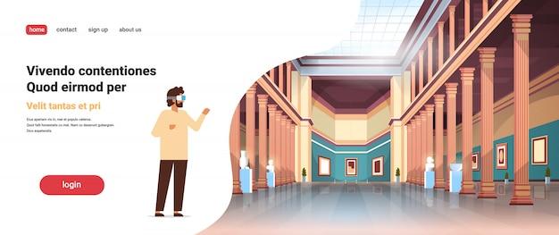 Uomo indossa occhiali digitali realtà virtuale classico museo storico sala galleria d'arte con colonne interni antichi reperti e collezione di sculture