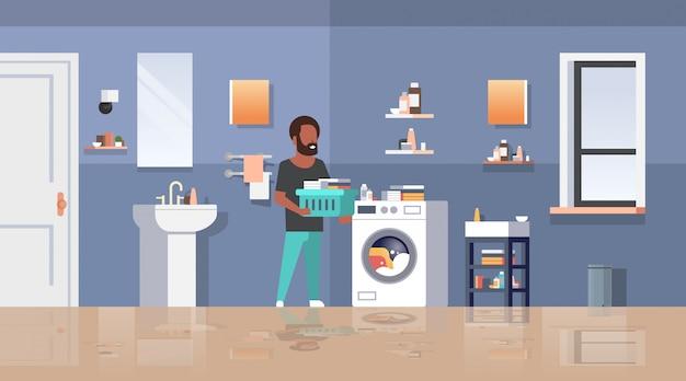 Uomo con il canestro di vestiti che sta vicino al tipo della lavatrice che fa lavori domestici lavanderia stanza da bagno moderna interno personaggio dei cartoni animati maschio orizzontale integrale