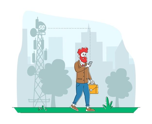 Uomo con il telefono cellulare passa dalla torre di trasmissione utilizzando internet per chattare